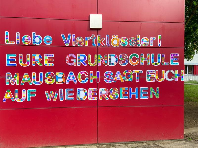 Eine rote Wand mit ausgeschnittenen Buchstaben: Liebe Viertklässler! Eure Grundschule Mausbach sagt euch auf Wiedersehen.