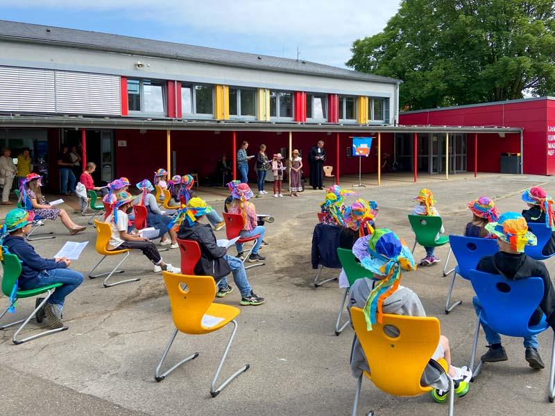 Eine Gruppe von Schulkindern sitzt auf bunten Stühlen auf dem Schulhof.