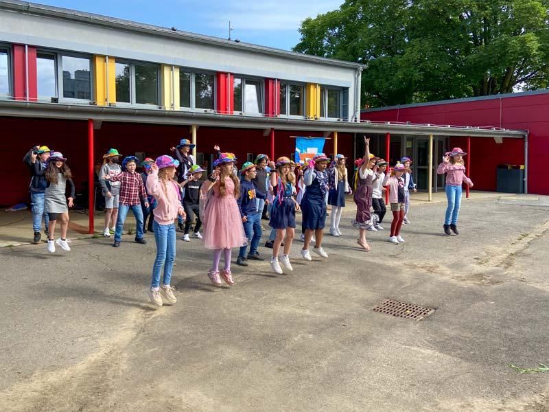 Eine Gruppe von Schulkindern mit bunten Hüten tanzt auf dem Schulhof.