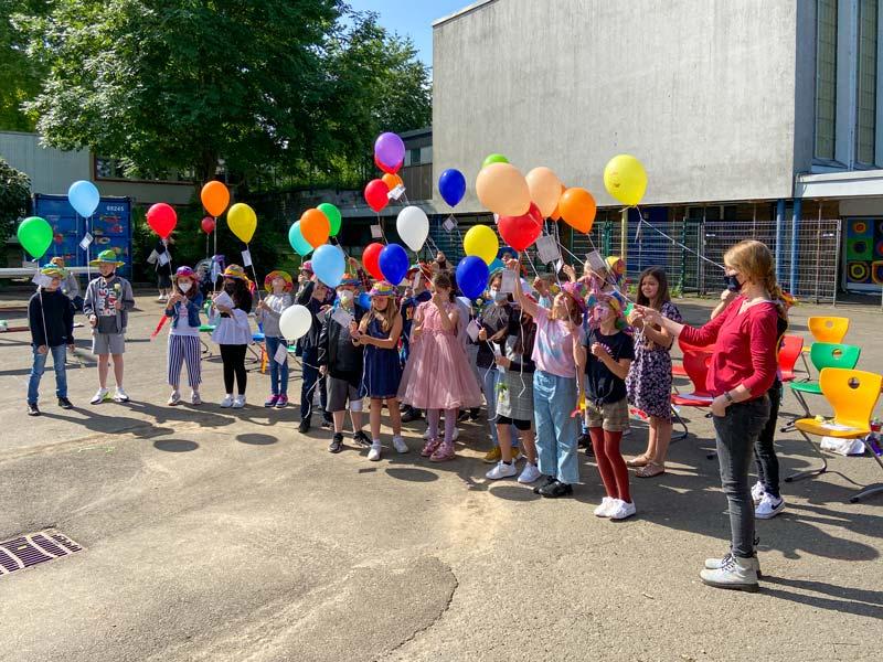 Eine Gruppe von Schulkindern und Lehrerin halten bunte Luftballons in der Hand.
